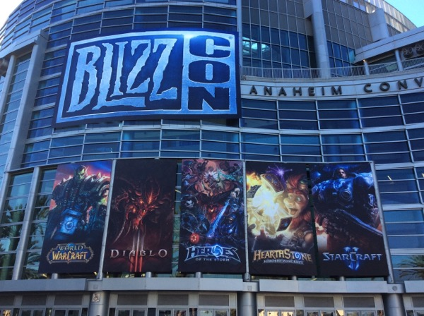 """A photo of the Anaheim Convention Center. A large sign says """"BlizzCon"""". Five banners below it highlight some of Blizzard's games."""