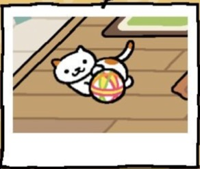 A white cat with a few brown spots plays with a ball that is made of fabric.
