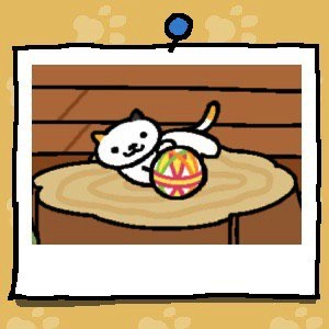 A white cat with one black ear and one yellow ear has a yellow spot at the end of their tail. They are playing with a fabric ball.