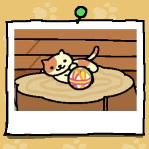 A yellow cat with light brown spots on their head, back and tail plays with a fabric ball.
