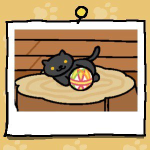 A black cat with yellow eyes plays with a fabric ball.