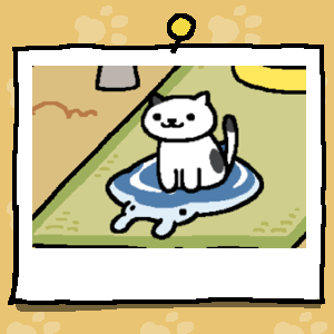 A white cat with a few black spots sits on a cooling mat that is shaped like a Manta Ray.