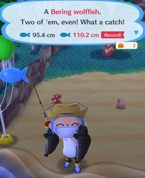 My Pocket Camp character is holding up two Bering wolffish.