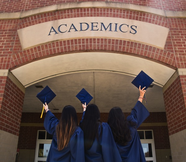 Three graduates hold up their hats outside brick building that says Academics. Photo by Leon Wu on Unsplash.