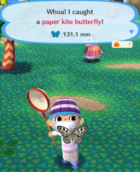 My Pocket Camp character holds up a large butterfly that is cream colored with a black design on its wings and body. It looks like it is made of paper and would make a good kite.