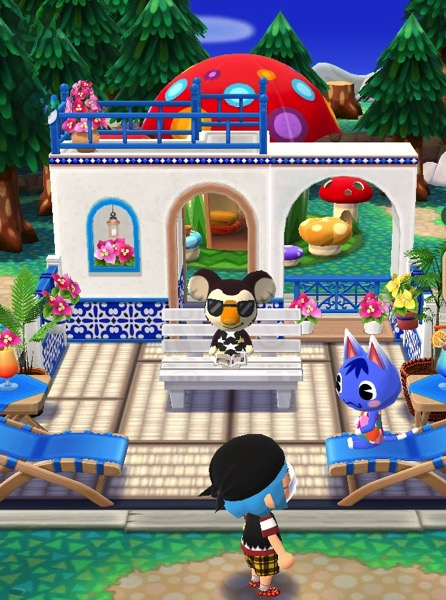 Two structures are merged together in the background. Both are white with blue accents. A rounded doorway allows access through them. In front are several beach-like chairs, some plants, and a white bench. A few animal friends are making use of them.