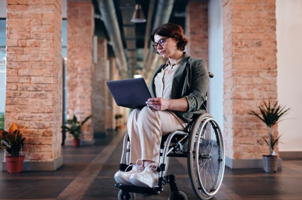 Photo of a woman looking at a laptop. She is using a wheelchair. Photo by Marcus Aurelius from Pexels.