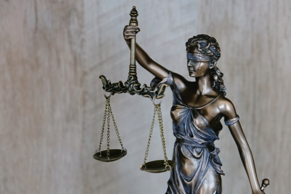 A cropped photo that shows the upper half of a justice statue. She is blindfolded and holding up a scale that is perfectly balanced. Photo by Tingey Injury Law Firm on Unsplash