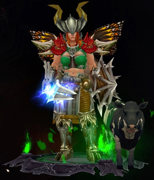 A female Barbarian wears a horned helmet, butterfly wings, and a mix of armor. Her shield has spikes on it. He sword shoots lightning. Next to her is a small calf.