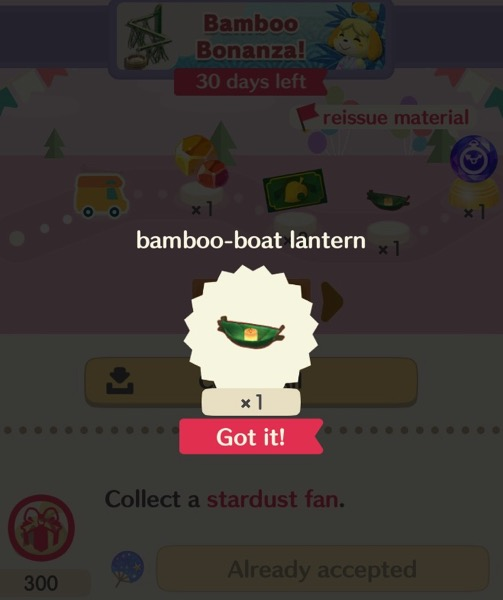A small, green, boat made out of bamboo, is in a circle shape. The boat has a lit candle inside it.