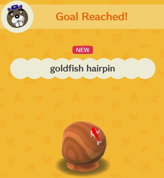 A wooden head (with no features) wears a hairpin that looks like a red and white goldfish.