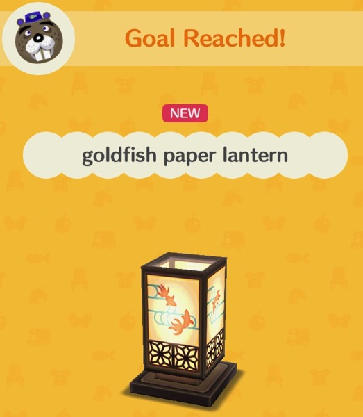 A rectangular paper lantern is decorated with silhouettes of goldfish that are swimming in water (represented by lines). The base of the lantern, and its corners, are made of wood.