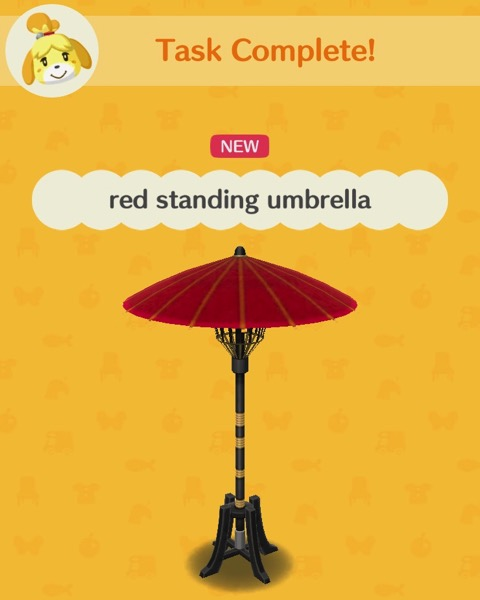 A tall umbrella with a red top is supported by four legs that the end of the umbrella has been placed into.