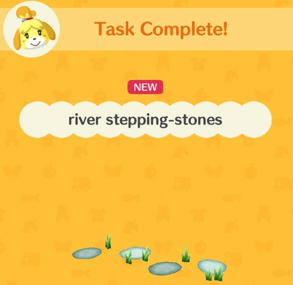 A box showing a small collection of river stepping stones. There is some grass around the stones.