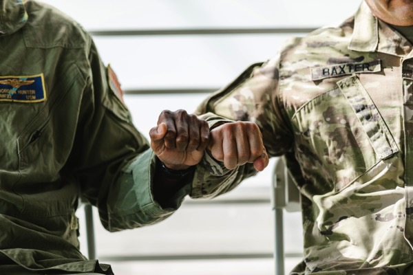 Two people in military uniforms doing a fist bump while seated next to each other. Photo by RODNAE Productions from Pexels