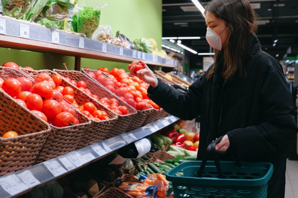 A woman wears a mask in the grocery store as she selects a tomato. She carries a small basket. Photo by Anna Shvets on Pexels