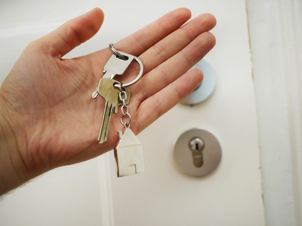 A person holds a set of keys with a keychain that looks like a house. Behind the hand is a slightly blurry door to a home. Photo by Maria Ziegler on Unsplash