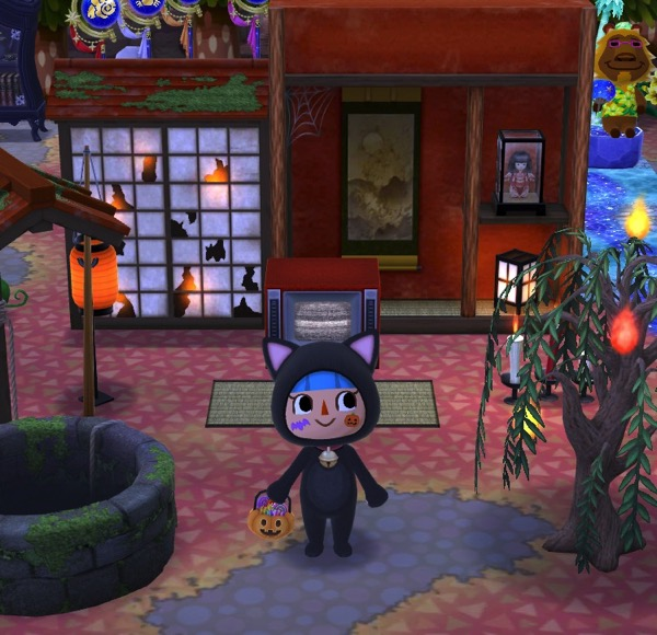 My Pocket Camp character wears a cat Halloween costume. They stand near the collection of Haunted Scavenger Hunt items.