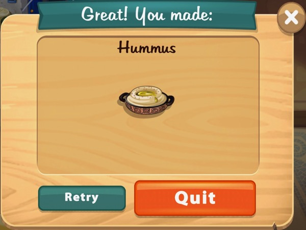 A small bowl with handles on either side holds some hummus.