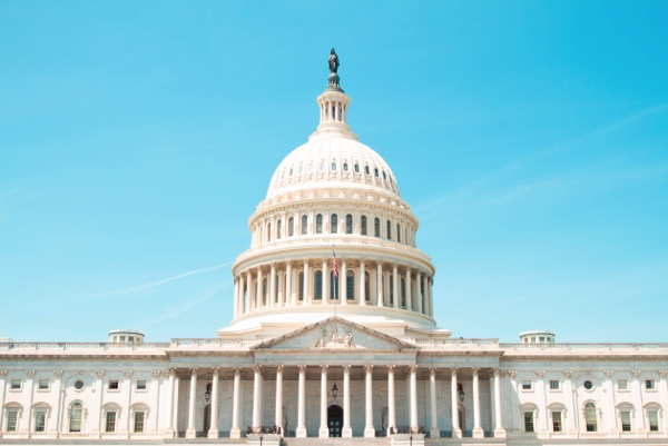 Photo of the United States Capitol under a light blue sky by Caleb Perez on Unsplash