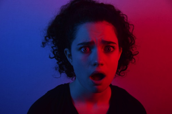 Woman with a shocked expression by Mason Kimbarovsky on Unsplash. Half of the woman's face is in red light, the other half is in blue light. She has curly dark hair.