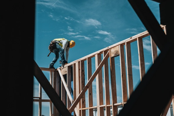 A construction worker wearing a hard hat is on top of the side of a building made of wood. The worker is building the home.